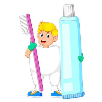 Un hombre con traje de dientes y sosteniendo un gran cepillo de dientes y una gran pasta de dientes.