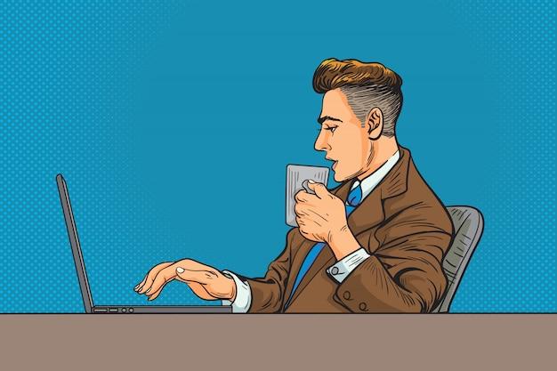 Hombre en traje de negocios y trabajando en una computadora portátil y tomando café