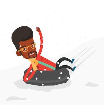 Hombre en trineo en tubo de goma de nieve en las montañas.