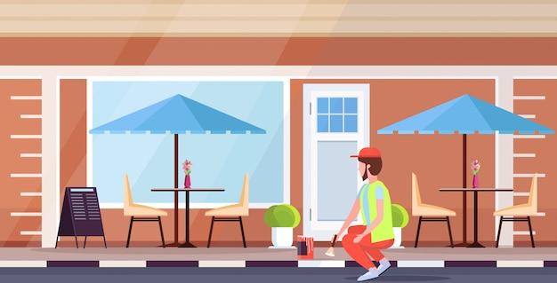 Hombre uniforme con pincel y cubo de pintura limpiador masculino pintura acera concepto de servicio de calle moderno edificio de café exterior plano de cuerpo entero horizontal