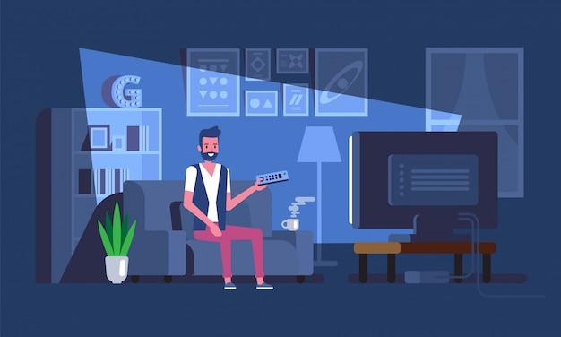 El hombre ve la televisión en el sofá por la noche