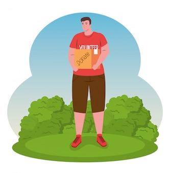 Hombre voluntario en hierba con caja de donación, caridad y concepto de donación de asistencia social