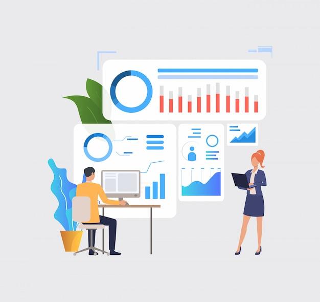 Hombres de negocios que analizan gráficos financieros en las computadoras