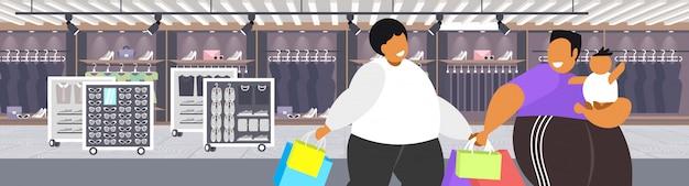 Hombres obesos gordos con niño sosteniendo bolsas de compras chicos con sobrepeso con niño pequeño caminando juntos gran venta concepto de obesidad moderno boutique tienda de moda retrato interior