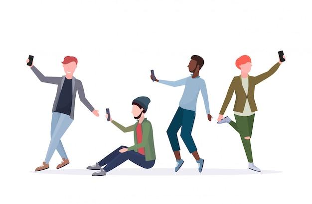 Hombres de raza mixta que toman una foto selfie en la cámara del teléfono inteligente personaje de dibujos animados masculino casual de pie juntos en diferentes poses fondo blanco de longitud completa horizontal