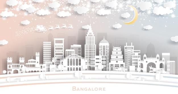 Horizonte de la ciudad de bangalore india en estilo de corte de papel con copos de nieve, luna y guirnalda de neón