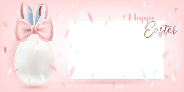 Huevo blanco de pascua con bunny bow y tarjeta del blanc en el fondo rosado. plantilla para un saludo cordial