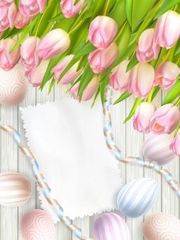 Huevo de pascua, tulipanes y tarjeta vintage vacía.