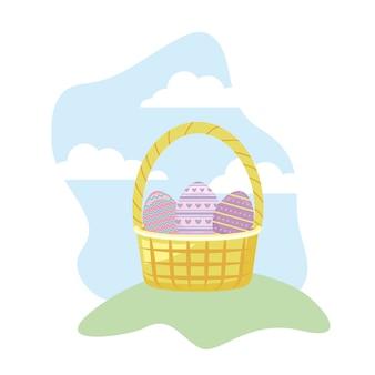 Huevos de pascua con cesta de mimbre en pasto.