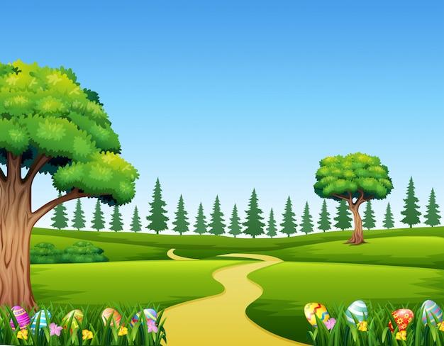 Huevos de pascua coloridos en hierba verde con paisaje hermoso