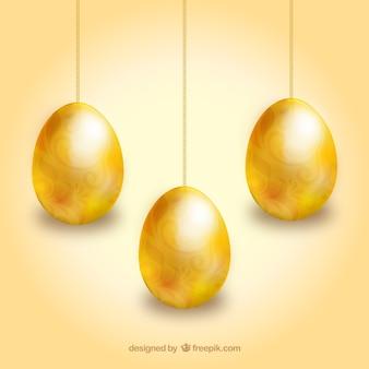 Huevos de pascua de oro colgando de cadenas