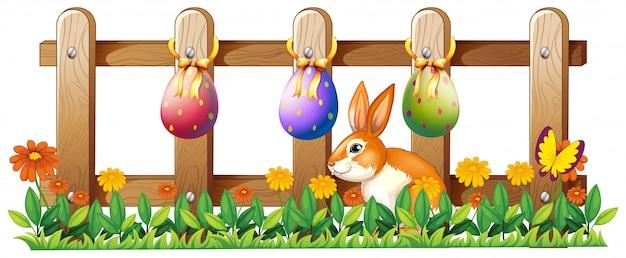 Huevos de pascua en la valla y un conejito