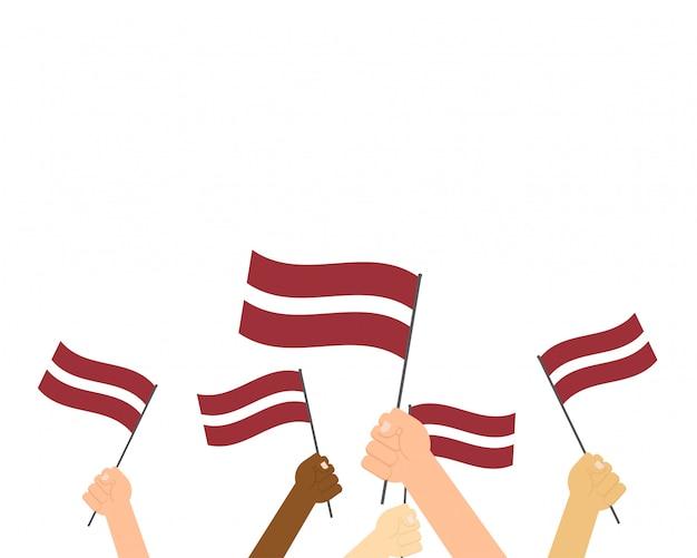 Ilustración de manos sosteniendo banderas de letonia