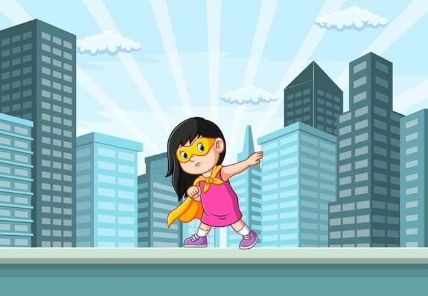 La ilustración de la niña de superhéroes y posando en la ciudad cerca del edificio.