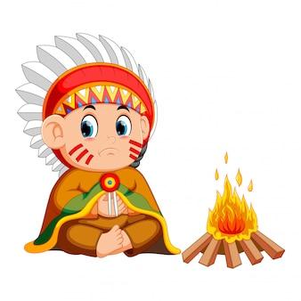 Indio norteamericano masculino sentado ante un incendio