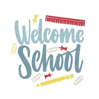 Inscripción de la escuela de bienvenida escrita a mano con un elegante guión y decorada con clips de papel, alfileres y regla esparcidos por todas partes.