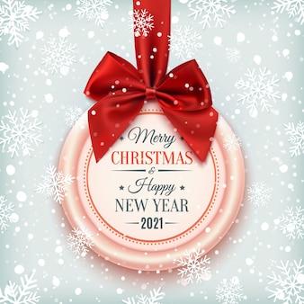 Insignia de feliz navidad y próspero año nuevo, con cinta roja y lazo sobre fondo de invierno con nieve y copos de nieve.