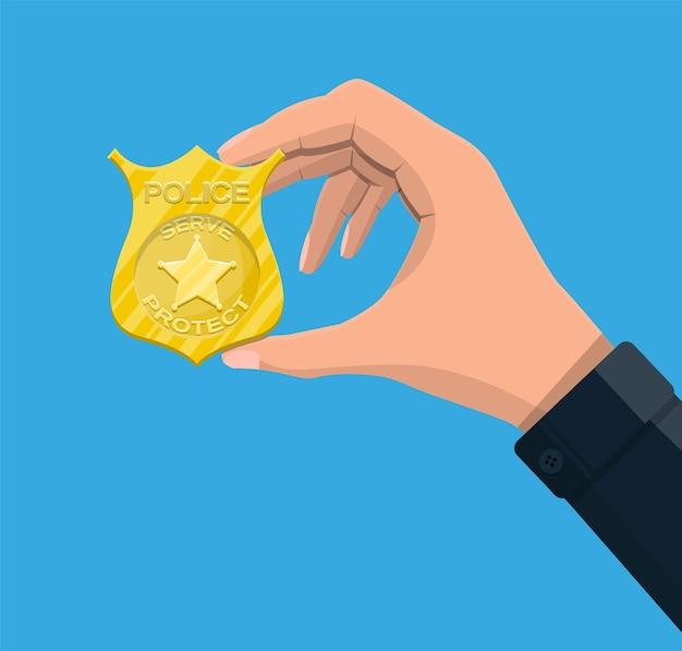 Insignia de oficial de policía en mano. emblema dorado brillante.