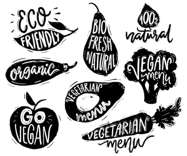 Insignias y pegatinas de menú vegetariano para cafeterías y restaurantes. texto vegano en las etiquetas de verduras para productos naturales. brócoli, aguacate, zanahoria dibujados a mano siluetas con letras.