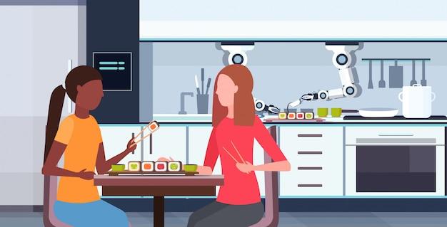 Inteligente práctico chef robot preparando sushi para raza mixta chicas pareja asistente robótico innovación tecnología concepto de inteligencia artificial moderno cocina interior horizontal retrato