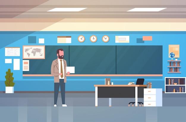 Interior de la sala de clase de la escuela con el profesor de sexo masculino standing over chalk board en el aula