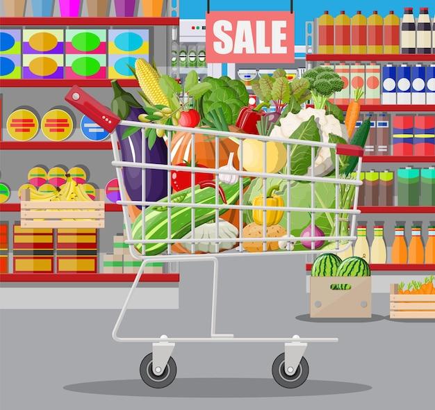 Interior de la tienda de supermercado con verduras en carrito de compras.