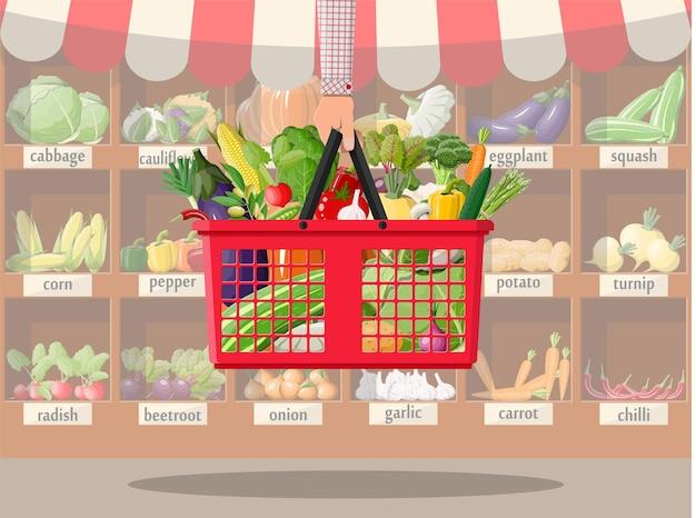 Interior de la tienda de supermercado con verduras en la cesta de la compra