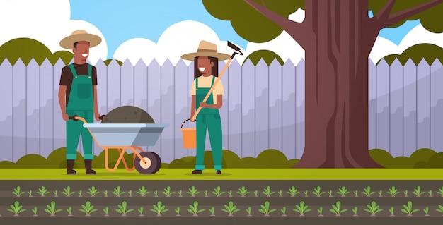 Jardinero hombre con carretilla de tierra mujer sosteniendo azada y cubo pareja agricultores concepto de jardinería patio trasero de fondo de tierras de cultivo horizontal