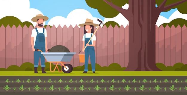 Jardinero hombre con carretilla de tierra mujer sosteniendo azada y cubo pareja agricultores plantar remolacha plantas hortalizas concepto jardinería patio trasero fondo de tierras de cultivo horizontal