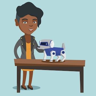 Joven africana jugando con un perro robótico.