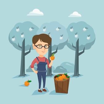 Joven agricultor caucásico recogiendo naranjas.