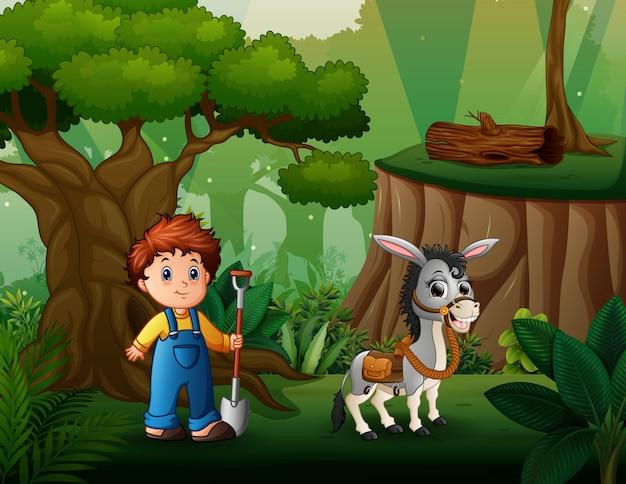 Joven agricultor pastoreando un burro en el bosque