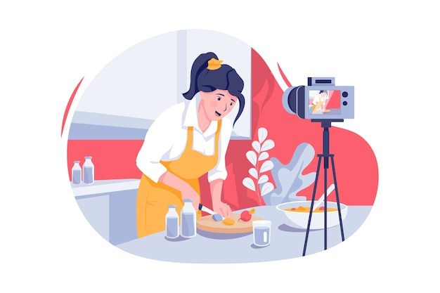 Joven asiática en la cocina grabando video en la cámara