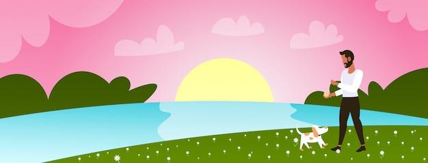 Joven caminando con perro al aire libre en park guy relajante con mascota concepto de tiempo de primavera