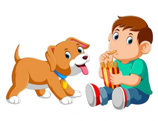 Joven comiendo papas fritas con un perro