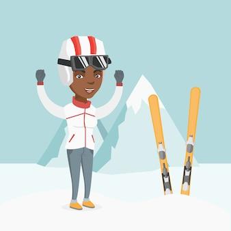 Joven esquiador africano de pie con las manos levantadas.