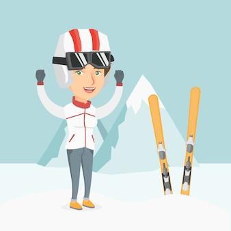 Joven esquiador caucásico de pie con las manos levantadas.
