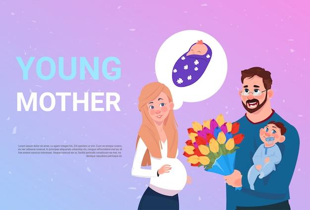 Joven madre embarazada con marido sosteniendo flores y pequeño hijo sobre fondo