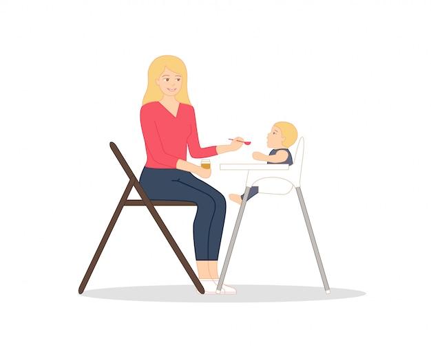 Joven madre está sentada en la silla con una cuchara y un frasco de puré de bebé en las manos