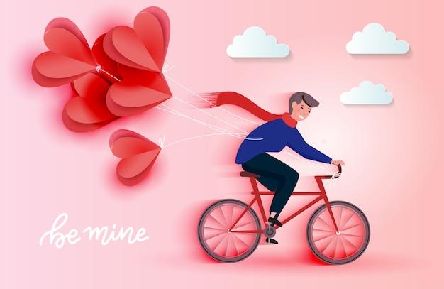 Joven montando bicicleta y sosteniendo globos de corte de papel de corazón rojo