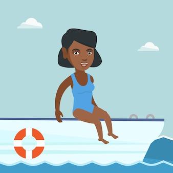 Joven mujer afroamericana broncearse en un velero