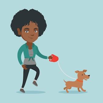 Joven mujer afroamericana caminando con su perro.