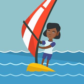 Joven mujer afroamericana windsurf.