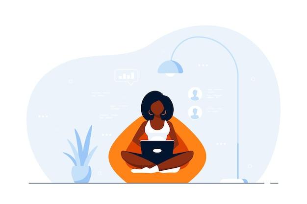 Joven mujer negra en casa sentado en una bolsa de silla y trabajando en equipo. trabajo remoto, oficina en casa, concepto de autoaislamiento. ilustración de estilo plano.