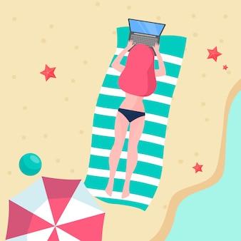 Joven mujer que trabaja con el portátil en la playa