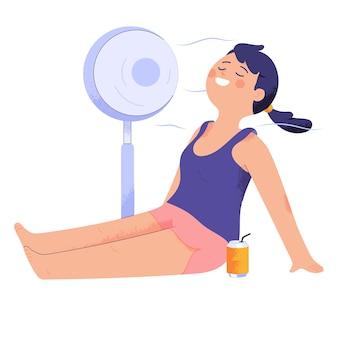 Joven mujer sentada en el suelo mientras disfruta del ventilador soplando y refresco frío
