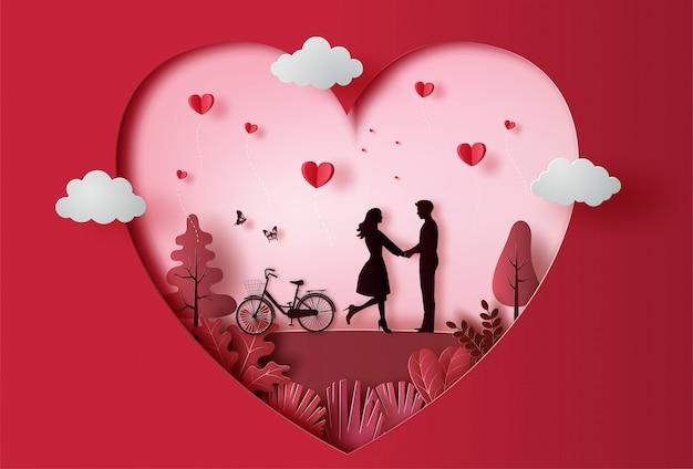 Joven pareja cogidos de la mano en el parque con muchos corazones flotantes, estilo de arte de papel.