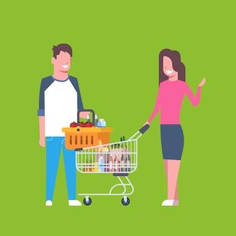 Joven pareja de compras con carrito y cesta llena de productos comestibles