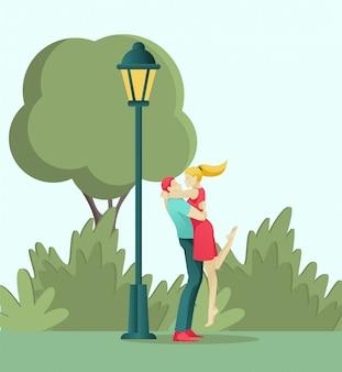 Joven pareja de enamorados besándose y abrazándose en el parque