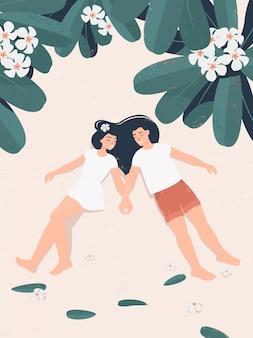 Joven pareja de enamorados se encuentran bajo un árbol de frangipani en flor